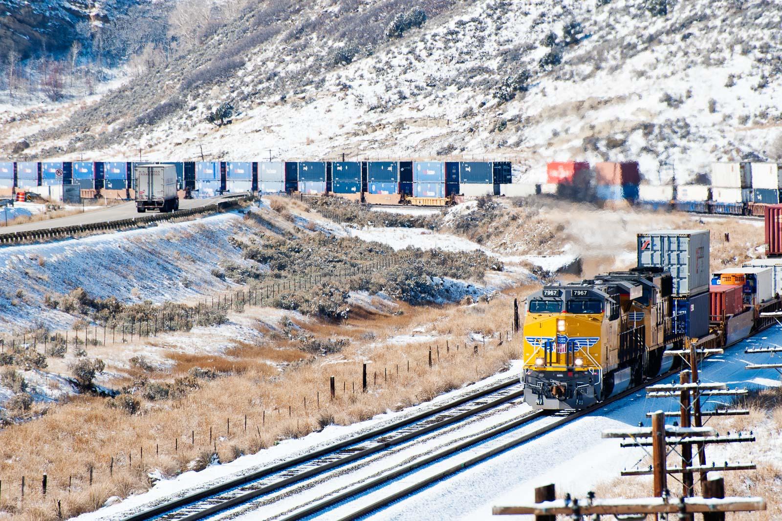 Güterzug in den USA mit Schnee und Trucks – Industriefoto